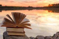 la-pile-du-livre-et-le-livre-cartonné-ouvert-réservent-sur-le-contexte-brouillé-de-paysage-de-nature-contre-le-ciel-de-coucher-57767997